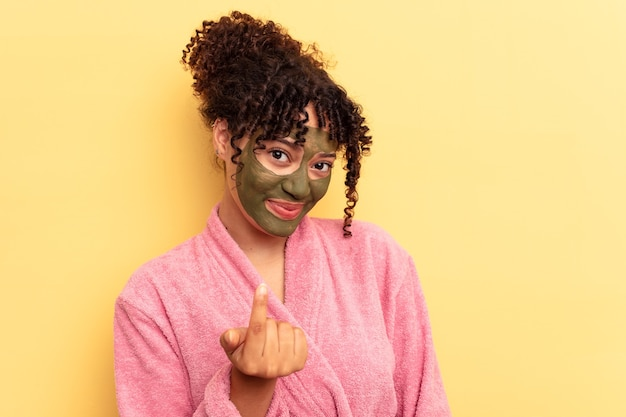 黄色の背景に分離された顔のマスクを身に着けている若い混血は、招待が近づくようにあなたに指を指しています。