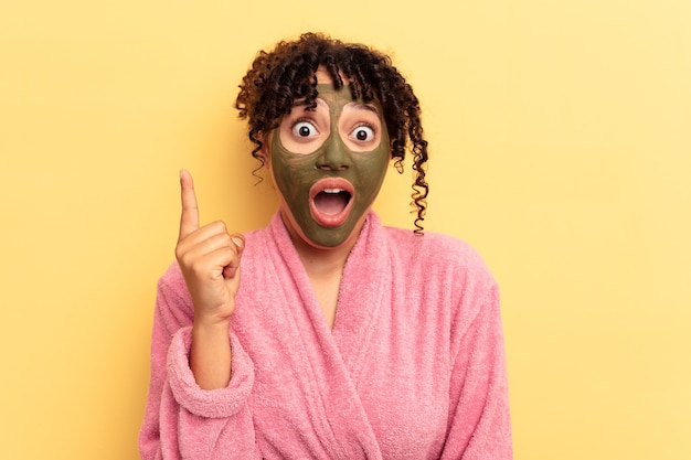 Young mixed race wearing facial mask isolated on yellow background having an idea, inspiration concept.