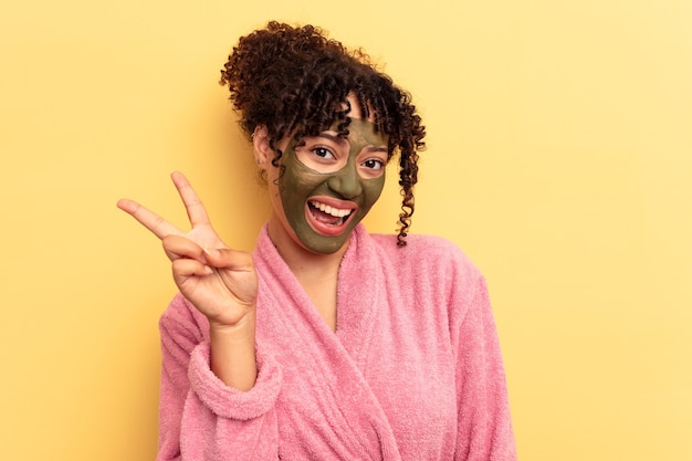 Young mixed race wearing facial mask isolated on yellow background joyful and carefree showing a peace symbol with fingers.