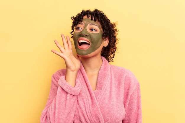 Young mixed race wearing facial mask isolated on yellow background shouting and holding palm near opened mouth.