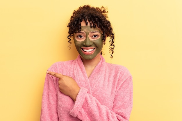 Young mixed race wearing facial mask isolated on yellow background smiling and pointing aside, showing something at blank space.