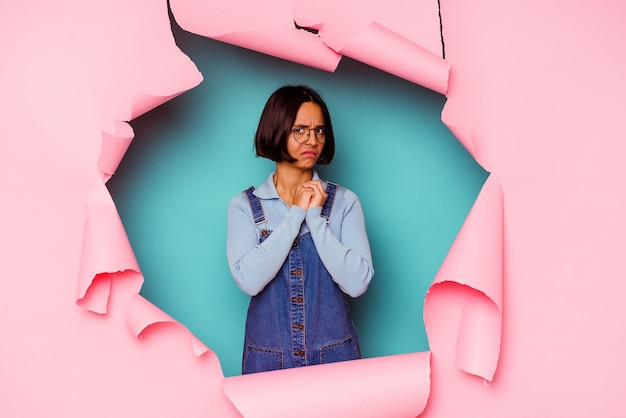 Young mixed race woman behind a broken background focused on a task, keeping forefingers pointing head.