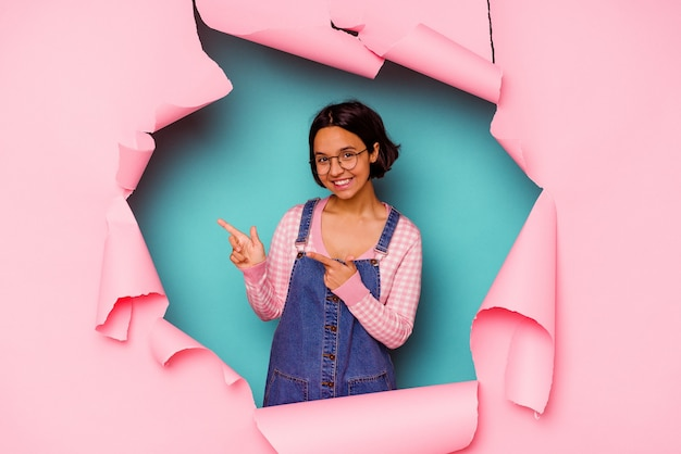 Young mixed race woman behind a broken background hugs, smiling carefree and happy.
