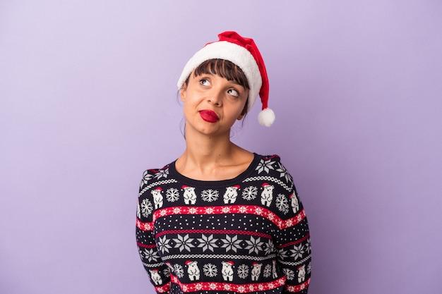 目標と目的を達成することを夢見ている紫色の背景に分離されたクリスマスを祝う若い混血の女性
