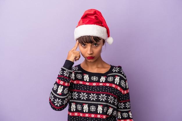 Молодая женщина смешанной расы празднует рождество изолированной на фиолетовом фоне указывая храм пальцем, думая, сосредоточился на задаче.