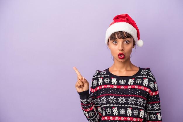 側面を指す紫色の背景に分離されたクリスマスを祝う若い混血の女性