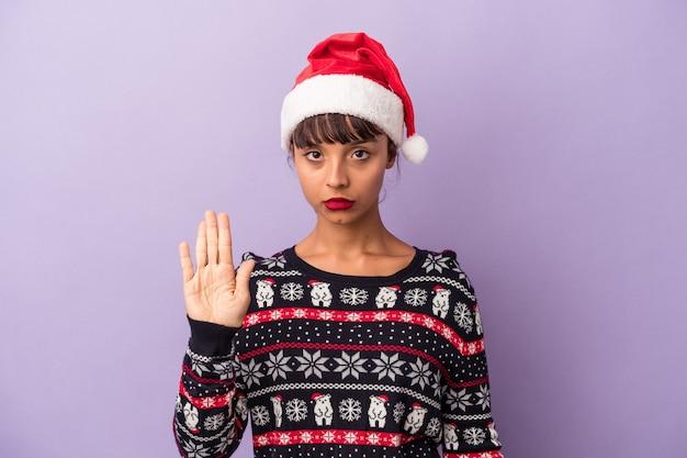 一時停止の標識を示す伸ばした手で立っている紫色の背景に分離されたクリスマスを祝う若い混血の女性は、あなたを防ぎます。