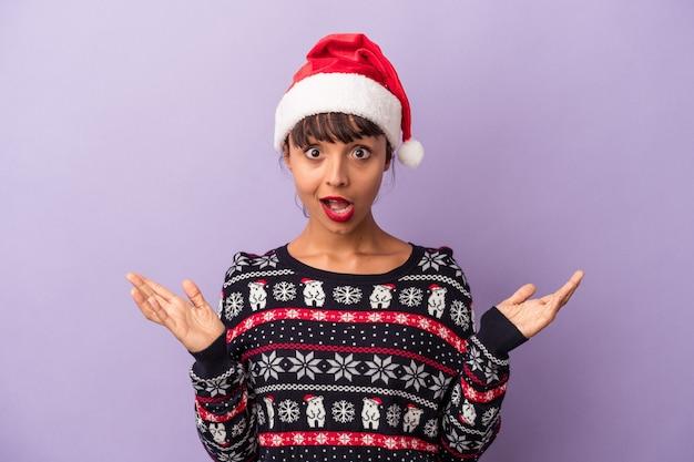 紫色の背景に分離されたクリスマスを祝う若い混血の女性は驚いてショックを受けました。