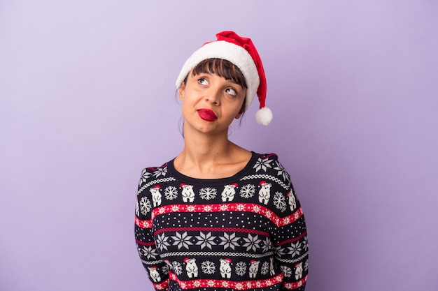 Young mixed race woman celebrating christmas isolated on purple background  dreaming of achieving goals and purposes