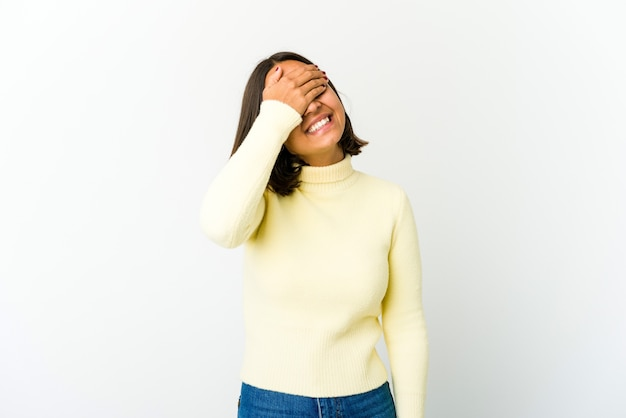 Young mixed race woman covers eyes with hands, smiles broadly waiting for a surprise.