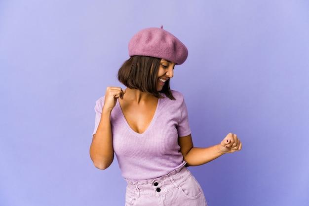 Молодая женщина смешанной расы танцует и веселится.