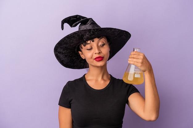 Молодая женщина смешанной расы, замаскированная под ведьму, празднует хэллоуин, держа зелье на фиолетовом фоне