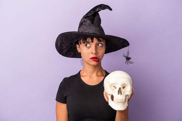 Молодая женщина смешанной расы, замаскированная под ведьму, держащую череп, изолированную на фиолетовом фоне, смущена, чувствует себя сомнительной и неуверенной.
