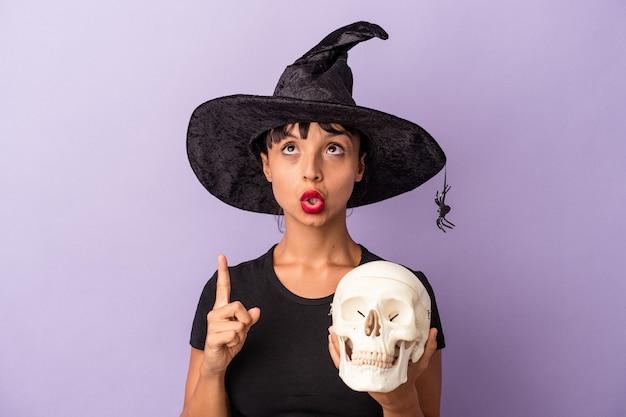 Молодая женщина смешанной расы, замаскированная под ведьму, держит череп, изолированный на фиолетовом фоне, указывая вверх с открытым ртом.
