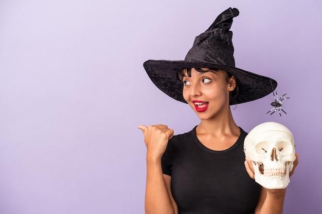 紫色の背景に孤立した頭蓋骨を持っている魔女を装った若い混血の女性が、親指の指を離して、笑いながらのんびりとしています。
