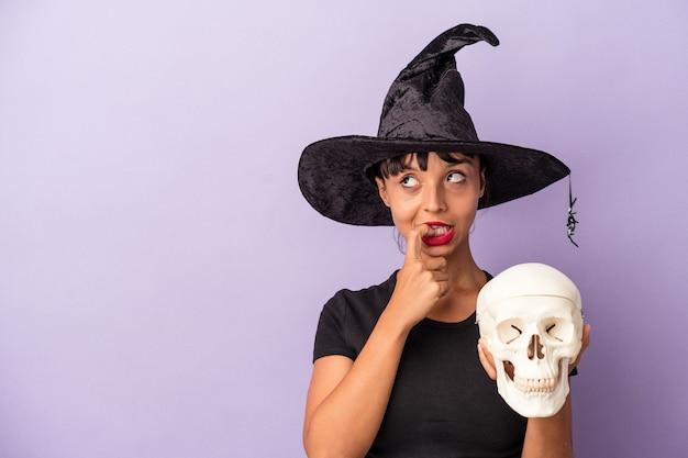 Молодая женщина смешанной расы, замаскированная под ведьму, держащую череп, изолированную на фиолетовом фоне, расслабилась, думая о чем-то, глядя на пространство для копирования.