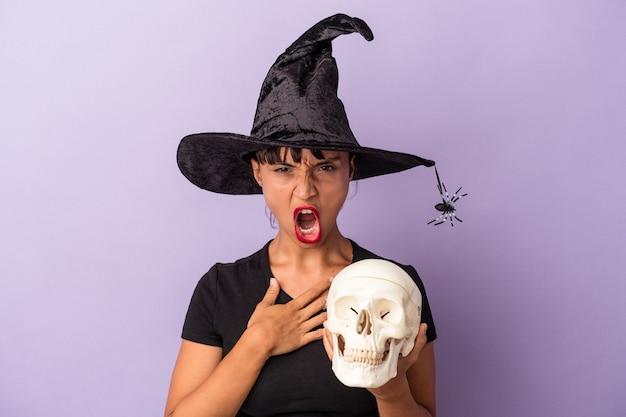 마녀로 변장한 젊은 혼혈 여성은 보라색 배경에 격리된 두개골을 들고 매우 화나고 공격적으로 비명을 지르고 있습니다.