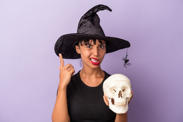 人差し指で失望のジェスチャーを示す紫色の背景に分離された頭蓋骨を保持している魔女を装った若い混血の女性。