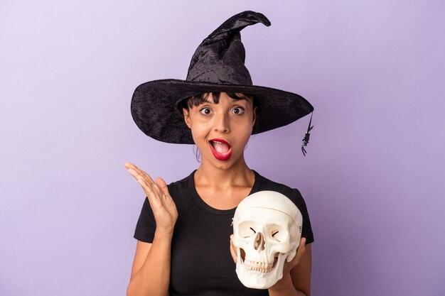 Молодая женщина смешанной расы, замаскированная под ведьму, держащую череп, изолированную на фиолетовом фоне, удивлена и шокирована.