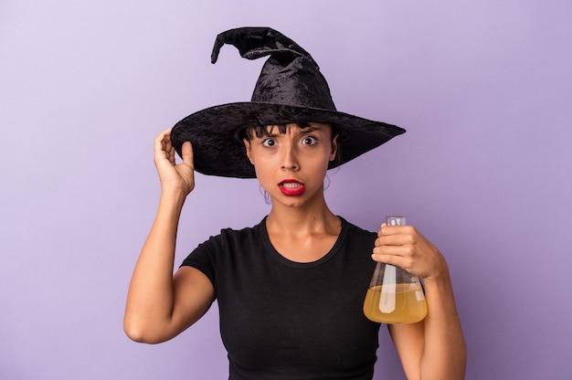 紫色の背景に隔離されたポーションを持った魔女に扮した若い混血の女性がショックを受け、重要な出会いを思い出しました。