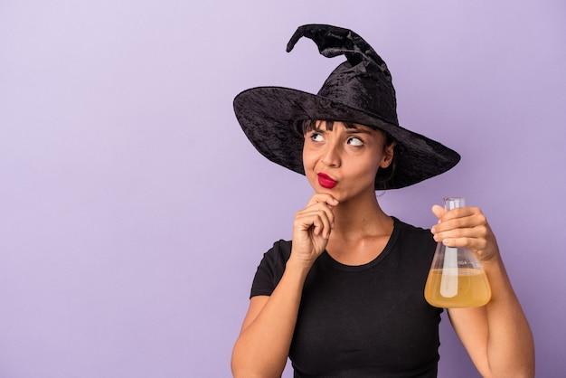 Молодая женщина смешанной расы, замаскированная под ведьму, держащую зелье, изолированную на фиолетовом фоне, смотрит в сторону с сомнительным и скептическим выражением лица.