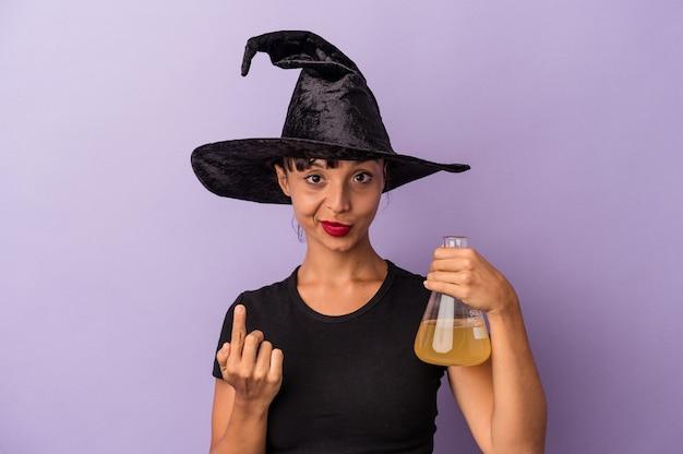 紫の背景に隔離されたポーションを持った魔女に扮した若い混血の女性が、誘うように指であなたを指さします。