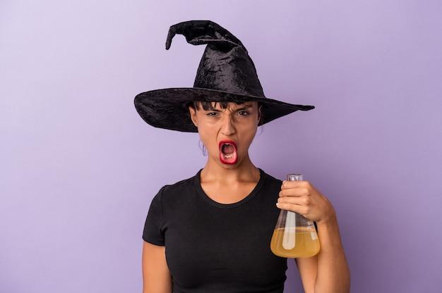 보라색 배경에 격리된 물약을 들고 마녀로 위장한 젊은 혼혈 여성이 매우 화나고 공격적으로 비명을 질렀습니다.