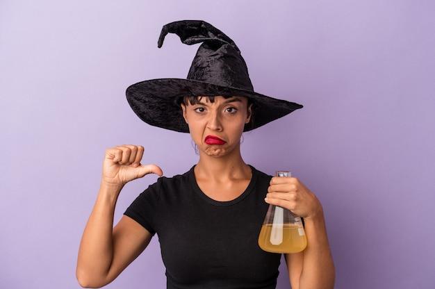 嫌いなジェスチャーを示す紫色の背景に分離されたポーションを保持している魔女を装った若い混血の女性は、親指を下に向けます。不一致の概念。