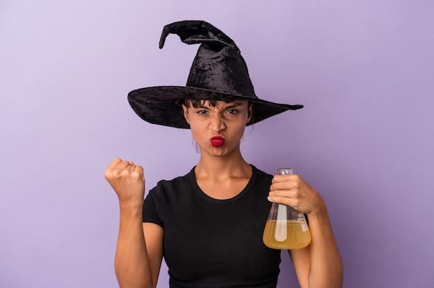 보라색 배경에 격리된 물약을 들고 마녀로 위장한 젊은 혼혈 여성이 카메라에 주먹을 대는 모습, 공격적인 표정을 하고 있습니다.