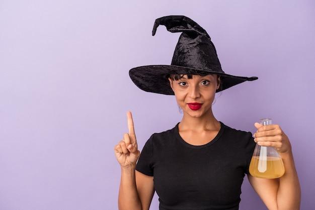 指でナンバーワンを示す紫色の背景に分離されたポーションを保持している魔女を装った若い混血の女性。