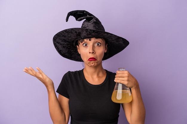 紫色の背景に分離されたポーションを持っている魔女を装った若い混血の女性は、肩をすくめ、目を開けて混乱しました。