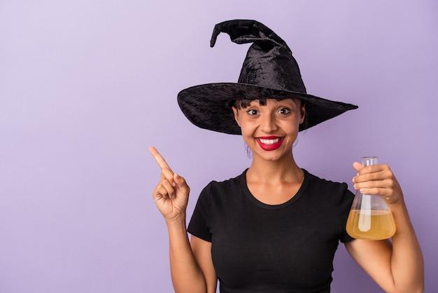 紫色の背景に分離されたポーションを持った魔女を装った若い混血の女性が笑顔で脇を向いて、空白のスペースで何かを示しています。