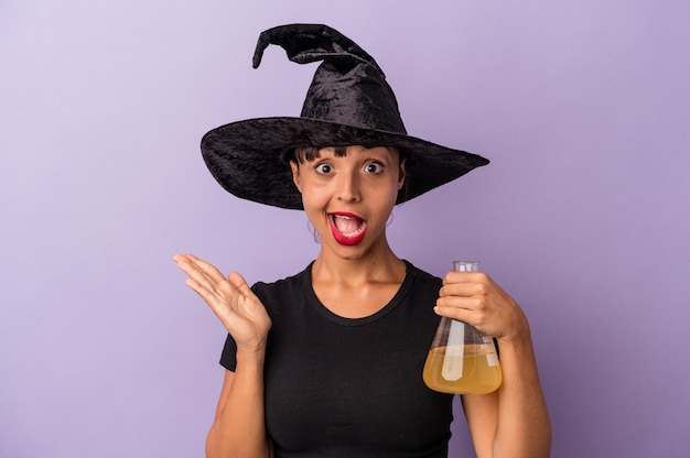 Молодая женщина смешанной расы, замаскированная как ведьма, держащая зелье, изолированное на фиолетовом фоне, удивлена и шокирована.