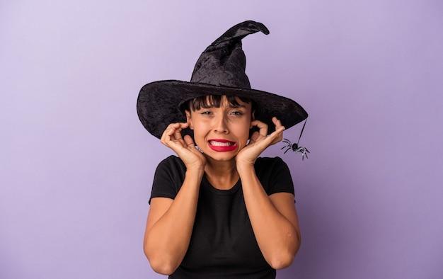手で耳を覆う紫色の背景に隔離された魔女を装った若い混血の女性。
