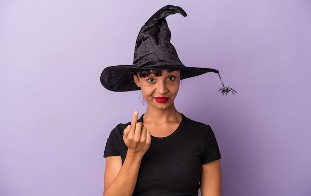 紫色の背景に孤立した魔女に扮した若い混血の女性が、誘うように指であなたを指さします。