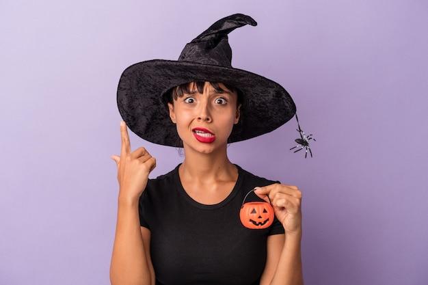 人差し指で失望のジェスチャーを示す紫色の背景に分離された魔女を装った若い混血の女性。