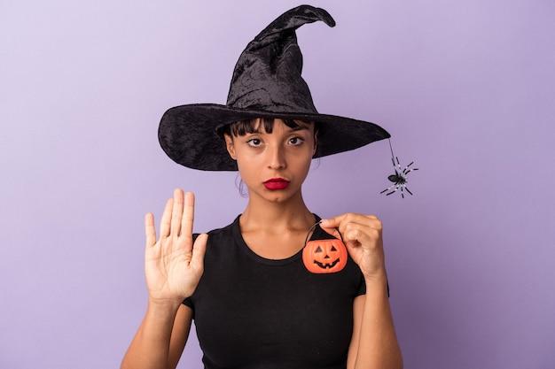 Молодая женщина смешанной расы, замаскированная под ведьму, изолирована на фиолетовом фоне, стоя с протянутой рукой, показывая знак остановки, предотвращая вас.