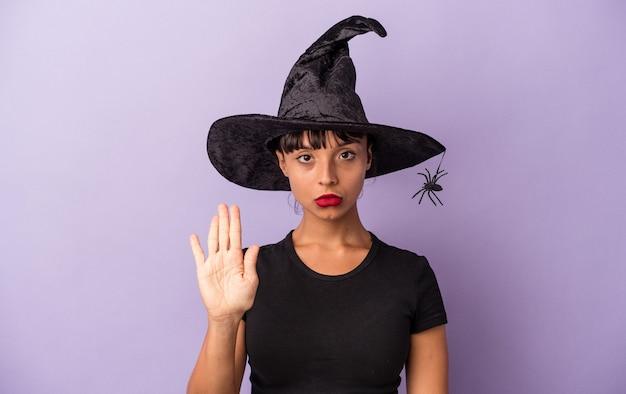 紫色の背景に孤立した魔女を装った若い混血の女性が、一時停止の標識を示している手を伸ばして立って、あなたを妨げています。