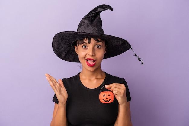 紫色の背景に孤立した魔女を装った若い混血の女性は驚いてショックを受けました。