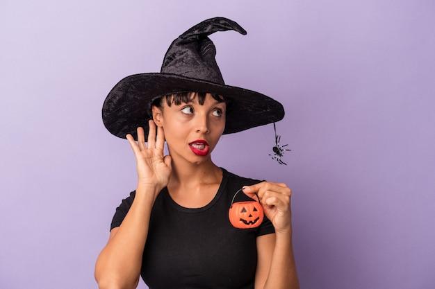 ゴシップを聴こうとしている紫色の背景に孤立した魔女を装った若い混血の女性。