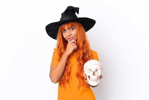 白い背景の思考で隔離の頭蓋骨を保持している魔女を装った若い混血の女性