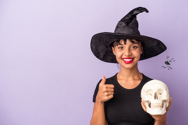 Young mixed race woman disguised as a witch holding a skull isolated on purple background  smiling and raising thumb up