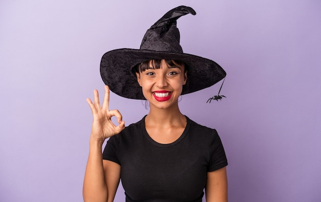 Young mixed race woman disguised as a witch isolated on purple background  cheerful and confident showing ok gesture.