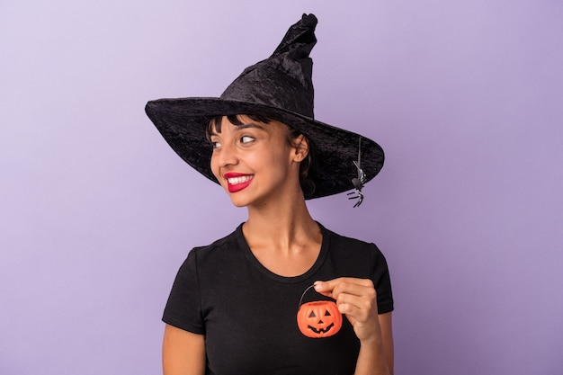 Young mixed race woman disguised as a witch isolated on purple background  looks aside smiling, cheerful and pleasant.