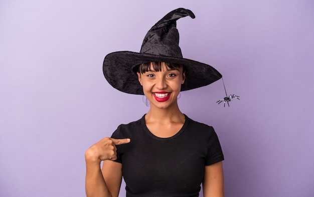 Young mixed race woman disguised as a witch isolated on purple background  person pointing by hand to a shirt copy space, proud and confident