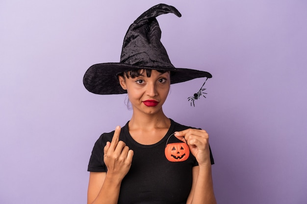 Young mixed race woman disguised as a witch isolated on purple background  pointing with finger at you as if inviting come closer.