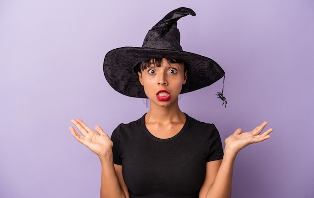 Young mixed race woman disguised as a witch isolated on purple background  surprised and shocked.