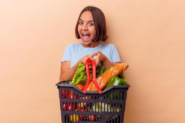 Молодая женщина смешанной расы делает покупки, изолированные на бежевой стене