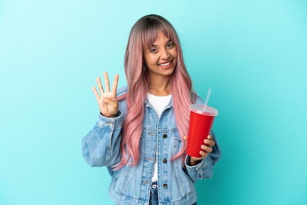 파란색 배경에 격리된 신선한 음료를 마시고 손가락으로 넷을 세는 젊은 혼혈 여성