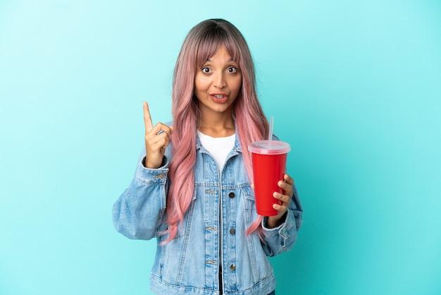 파란색 배경에 격리된 신선한 음료를 마시는 젊은 혼혈 여성은 손가락을 들어올리면서 해결책을 실현하려고 합니다.